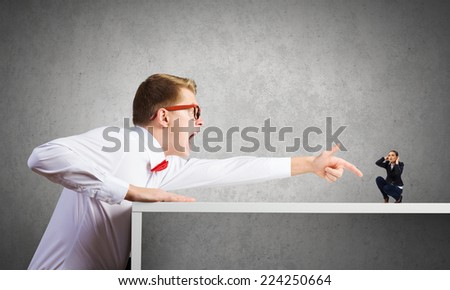 Angry businessman screaming at miniature of woman colleague - stock photo