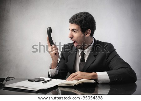Angry businessman screaming on the telephone - stock photo