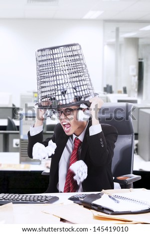 Angry businessman screaming while hold rubbish bin on his head in the office - stock photo