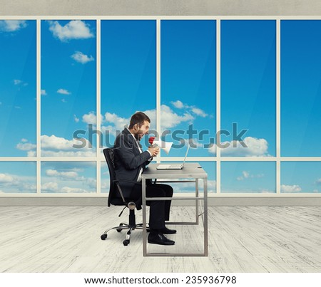angry businessman screaming with megaphone and looking at laptop in the light office with big windows - stock photo