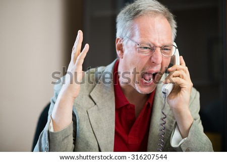 Angry businessman shouting on the phone - stock photo