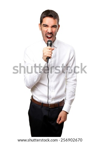 Angry businessman shouting with a microphone - stock photo