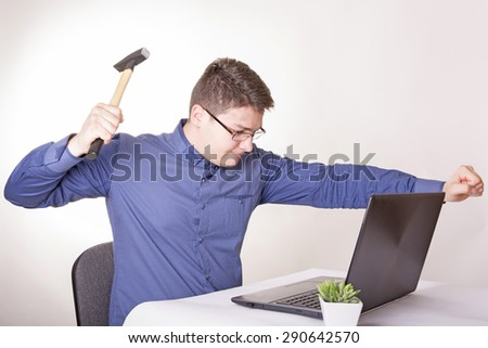 Angry businessman sitting at a desk in front of laptop - stock photo