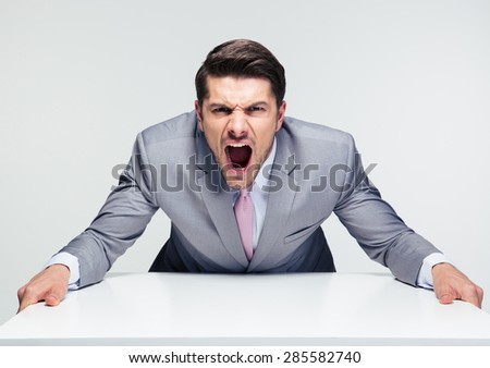 Angry businessman sitting at the table and screaming over gray background. Looking at camera - stock photo