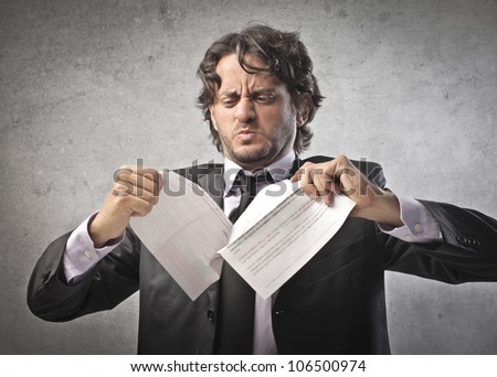 Angry businessman tearing a document to pieces - stock photo