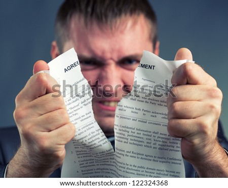 Angry businessman tearing agreement in pieces - stock photo