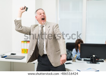 Angry businessman throwing away his mobile phone
