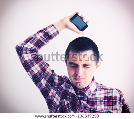 Angry businessman throwing his mobile phone - stock photo