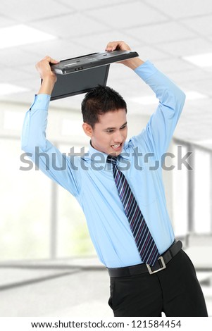 angry businessman trying to smash his laptop - stock photo