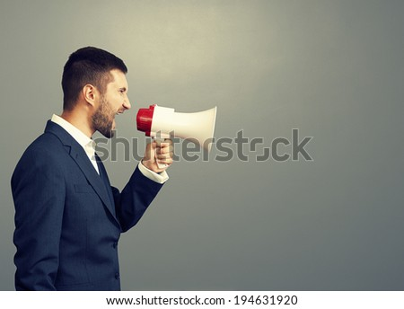 angry businessman using megaphone over grey background - stock photo