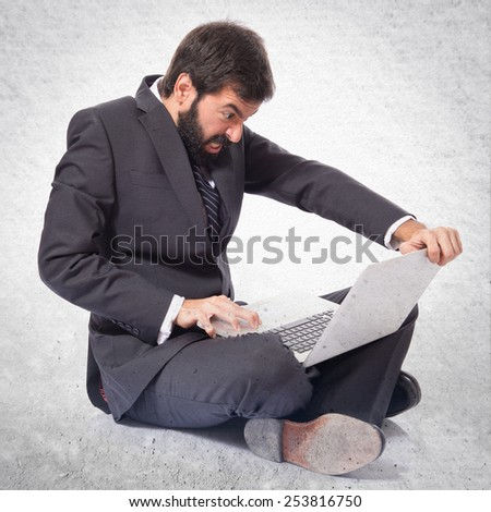 Angry businessman with laptop over textured background - stock photo