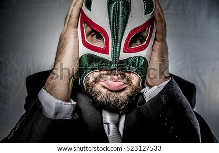Angry businessman with mask of Mexican fighter, dressed in suit and tie
