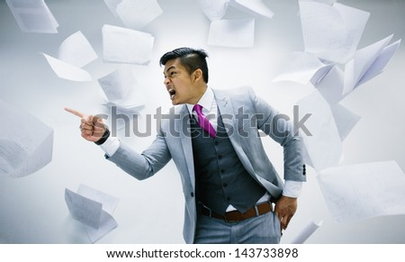 angry businessman with pile of papers flying on air - stock photo