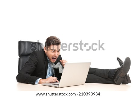 Angry businessman working at his laptop computer. man sitting on chair with feet on table and pulling tie