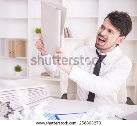 Angry businessman working in office and holding a paper - stock photo