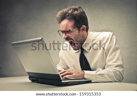 angry businessman working on the laptop