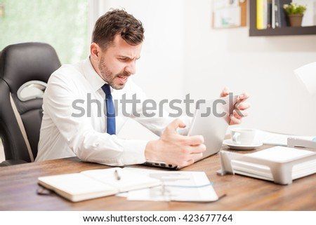 Angry businessman yelling and strangling his laptop computer in frustration to his slow internet connection at work - stock photo