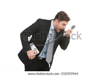 Angry businessman yelling into landline phone on white. Extreme angry man shouting at phone - stock photo