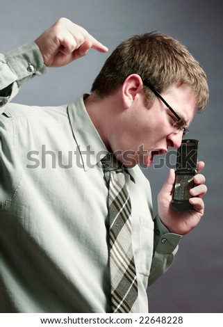 Angry businessman yelling on a phone conversation - stock photo