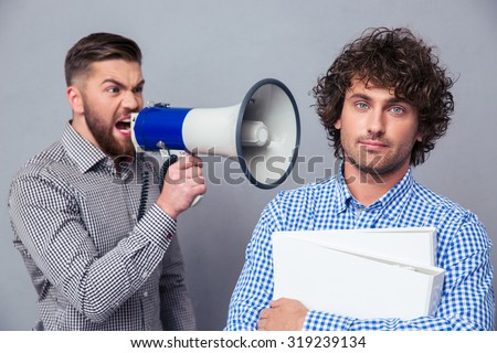 Angry businessman yelling via megaphone to another man over gray background - stock photo