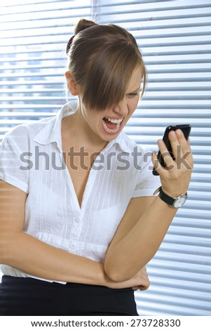 Angry businesswoman looking at a mobile phone - stock photo