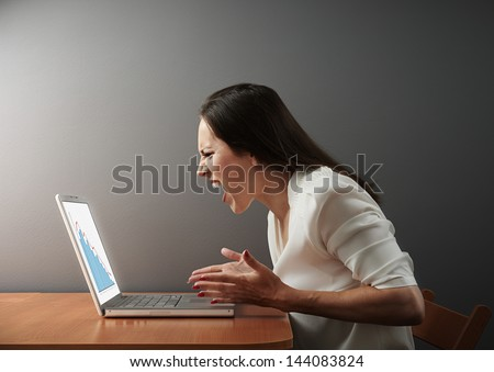angry businesswoman looking at negative statistic - stock photo