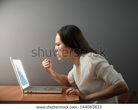 angry businesswoman looking at negative statistic and showing fist