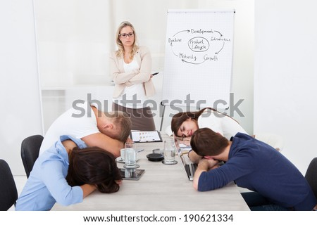 Angry businesswoman looking at tired colleagues sleeping during presentation in office - stock photo