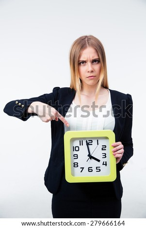 Angry businesswoman pointing finger on big clock over gray background and looking at camera - stock photo