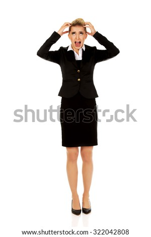 Angry businesswoman pulling her hair and screaming. - stock photo