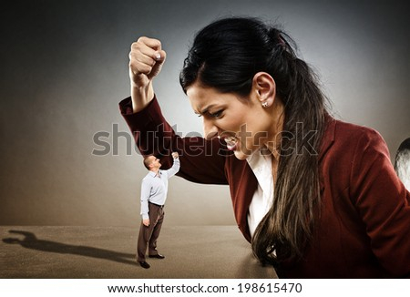 Angry businesswoman ready to crush the courageous subordinate who is confronting her - stock photo