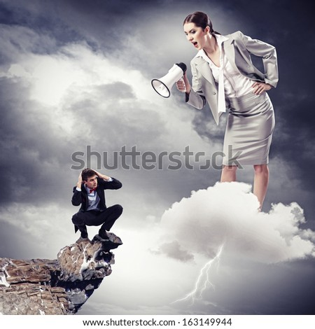 Angry businesswoman with megaphone shouting at colleague - stock photo