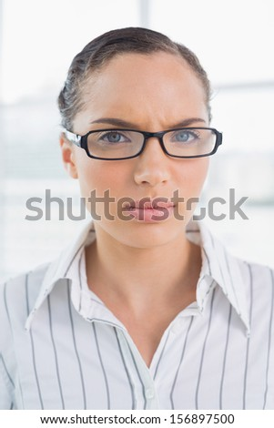 Angry businesswoman with reading glasses looking at camera