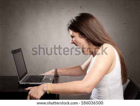 angry businesswoman working with a laptop at office - stock photo
