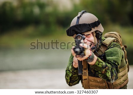 Angry Canadian soldier yelling and pointing a rifle at the camera