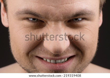 Angry caucasian man portrait on black background. closeup of young guy frowning and looking into camera - stock photo