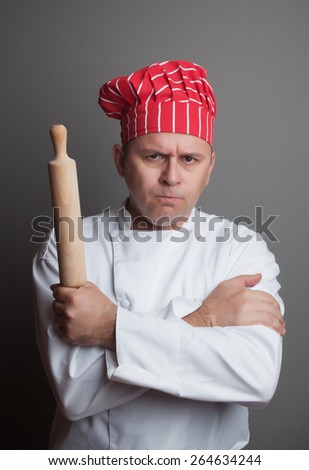 Angry chef with rolling pin, studio shot over gray background - stock photo