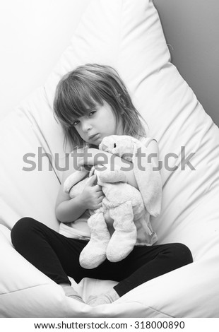 Angry child holding a soft rabbit
