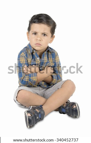 angry child sitting on the floor. on white background