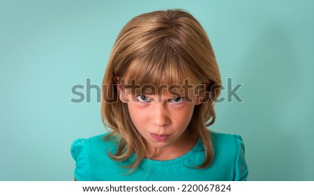 Angry child. Young girl with angry or upset expression on face on turquoise background. Negative human emotion facial expression. - stock photo