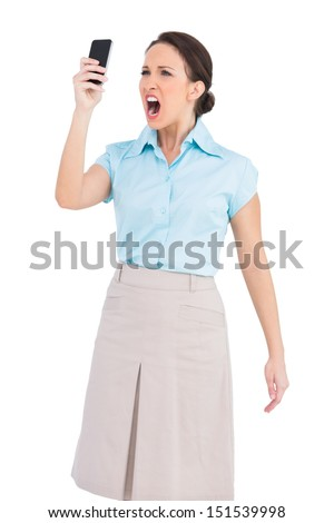 Angry classy businesswoman on white background shouting at her smartphone - stock photo