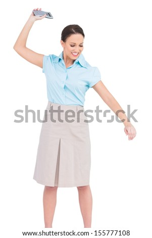 Angry classy businesswoman on white background throwing her calculator - stock photo