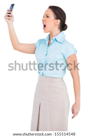 Angry classy businesswoman on white background yelling at her smartphone - stock photo
