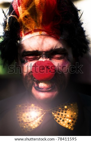 Angry Clown Face Featuring A Big Red  Nose And Vicious Teeth With Gold Polka Dot Tie - stock photo