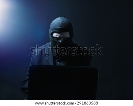 Angry computer hacker in suit stealing data from laptop in front of black background and blue light - stock photo