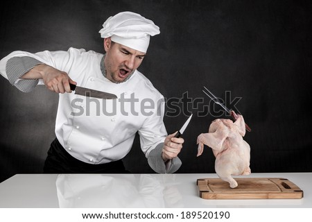 Angry cook fighting with knifes. Raw chicken attack - stock photo