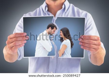 Angry couple facing off after argument against grey vignette