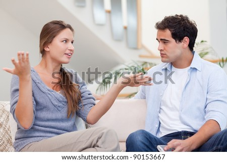 Angry couple having an argument in their living room - stock photo
