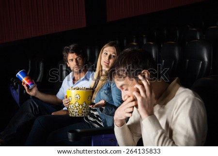 Angry couple looking at man using mobilephone while watching film in movie theater