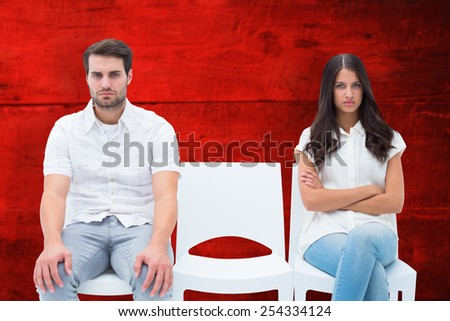 Angry couple not talking after argument against red wooden planks - stock photo